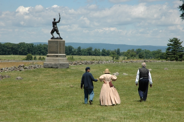 People in period dress approach the 72nd PA monument. Just a few days ago a thunderstorm knocked the statue off its base but park personnel quickly put it back.