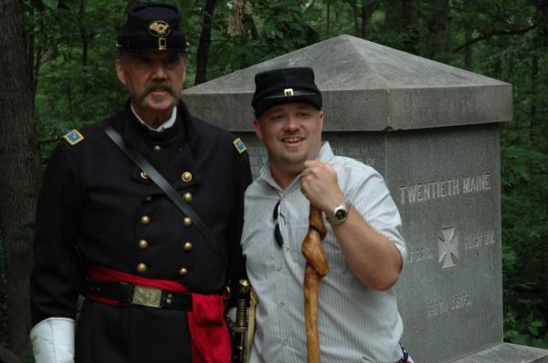 "A happy visitor to LIttle Round Top poses with ""Joshua Lawrence Chamberlain"" at the 20th Maine monument."