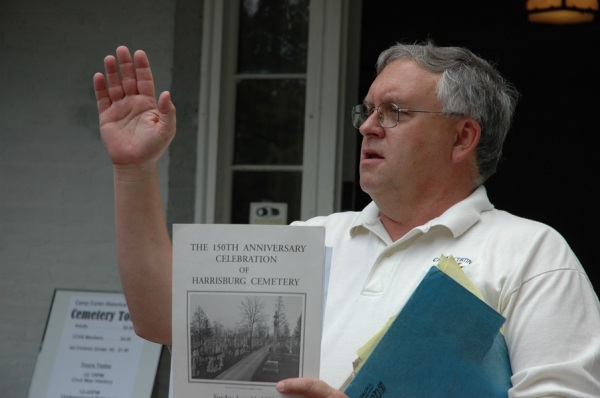 Jim Schmick shows us a brochure from the cemetery's 150th anniversary in 1995.