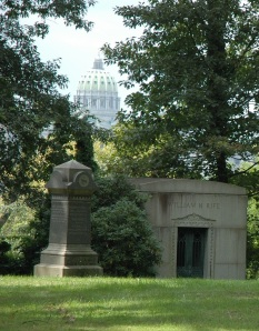 The Pennsylvania State Capitol is visible through the trees. George Grey Barnard, who created some of the statuary for the building, is buried here.