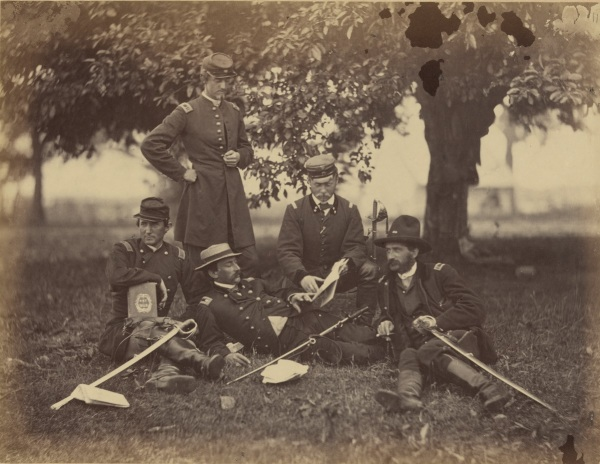 "Alexander Gardner took this photograph at Fairfax Court House in June 1863, just before the start of the Gettysburg Campaign. He called it ""Studying the Art of War."" Ulric Dahlgren is the man standing. The man in the center is Count Ferdinand von Zeppelin, in the United States to observer. He will later become famous for the airships he develops. At the far right is Lt. Rosencranz, who will later serve on Meade's staff. Theodore Lyman mentions him often in his writings. To read Gardner's extensive caption for this photo, see below (Library of Congress)."