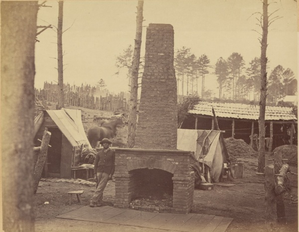 "Alexander Gardner called this photograph ""Breaking Camp.: It shows General George H. Sharpe's deserted headquarters at Brandy Station. Sharpe headed the army's Bureau of Military Information. Winter camp is over; the army is on the move (Library of Congress)."