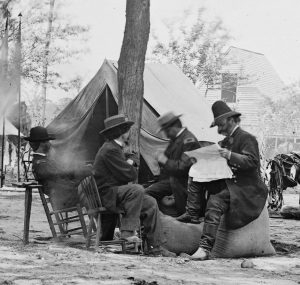Ambrose Burnside (reading paper) and staff at Cold Harbor, June 11 or 12, 1864. That's photographer Matthew Brady in the straw hat (Library of Congress).