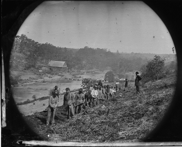 "Another one of O'Sullivan's images from May 24. Of this one he said, ""Jericho Mills, Va. Party of the 50th New York Engineers building a road on the south bank of the North Anna, with a general headquarters wagon train crossing the pontoon bridge"" (Library of Congress)."