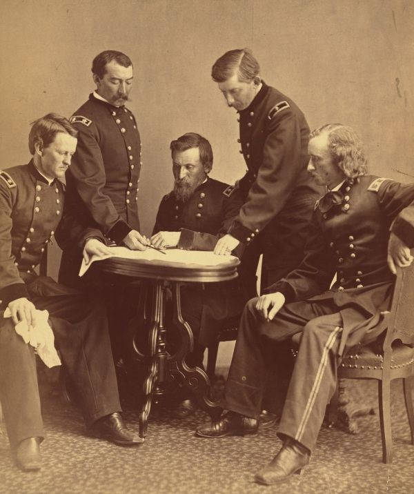 """Photograph showing Generals Wesley Merritt, Philip Sheridan, George Crook, James William Forsyth, and George Armstrong Custer around a table examining a document."" Click to enlarge (Library of Congress)."
