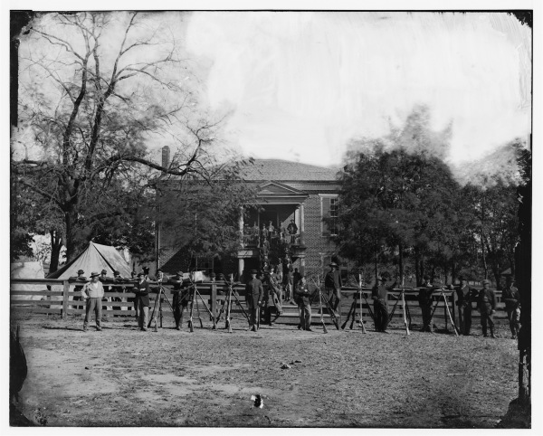 Federal soldiers and some civilians pose for a photograph in front of the building that gave Appomattox Court House its name. Click to enlarge (Library of Congress).