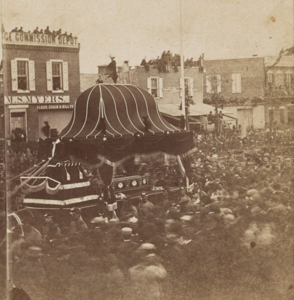 Photograph shows Abraham Lincoln's casket conveyed by funeral car through the crowd on Broad Street in Philadelphia, April 22, 1865 (Library of Congress).