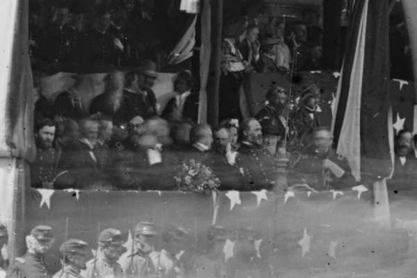 Detail of a photograph of the reviewing stand in front of the White House shows a number of VIPS, including (left to right) Ulysses S. Grant, the blurred figure of Edwiin Stanton, President Andrew Johnson, Wesley Merritt (as commander of the cavalry corps in Philip Sheridan's absence, he sat next to the president as his corps passed), Secretary of the Navy Gideon Welles, Postmaster William Dennison, William T. Sherman, and Quatermaster General Montgomery Meigs (Library of Congress).